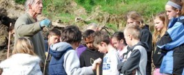 Plantsman Peter Morris gives a lesson in tree planting to Hautapu School pupils