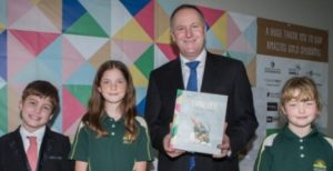 John Key was given a copy of the Divine Eats cookbook when he met Tamahere School students, from left, Thomas Gatley, Kristen Martinus, and Ava Lipinski.